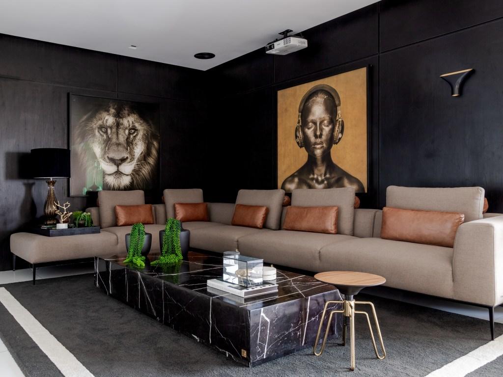 Living com sofá de canto marrom claro e almofadas em couro. Mesa de centro preta. Quadro de menina pintada de dourado com fones de ouvido. Quadro de foto de leão