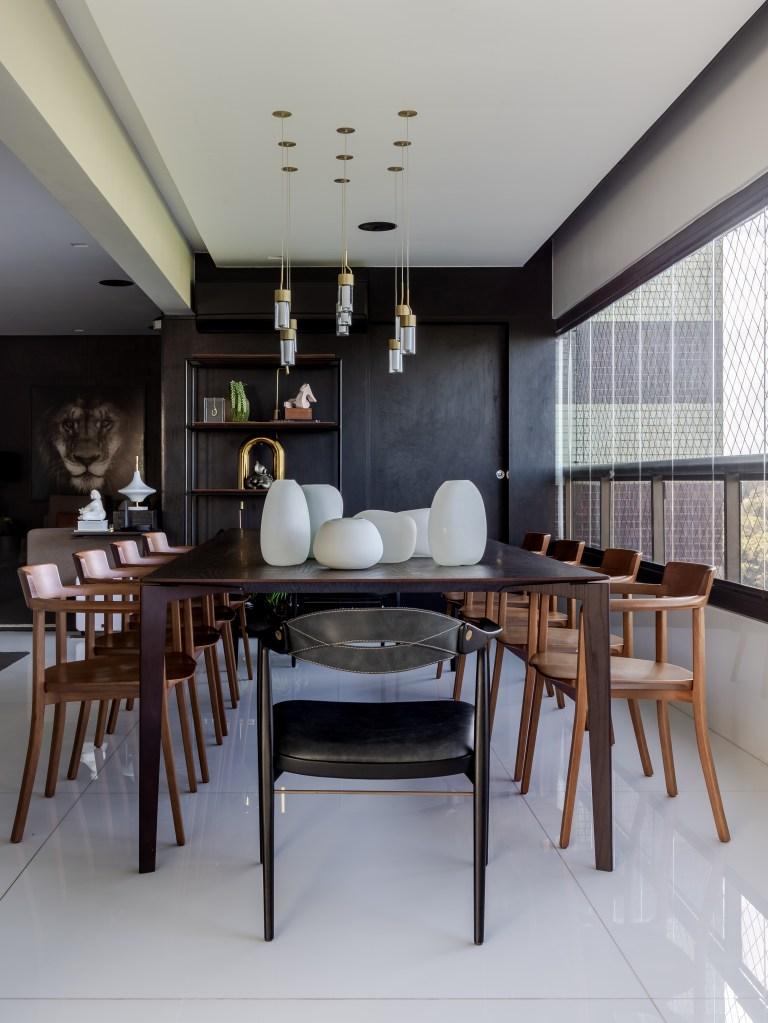 Mesa de jantar em madeira escura de 10 lugares. Cadeiras em madeira mais clara. Vasos arredondados brancos em cima. Pendentes dourados. Piso em porcelanato branco e parede do fundo preta