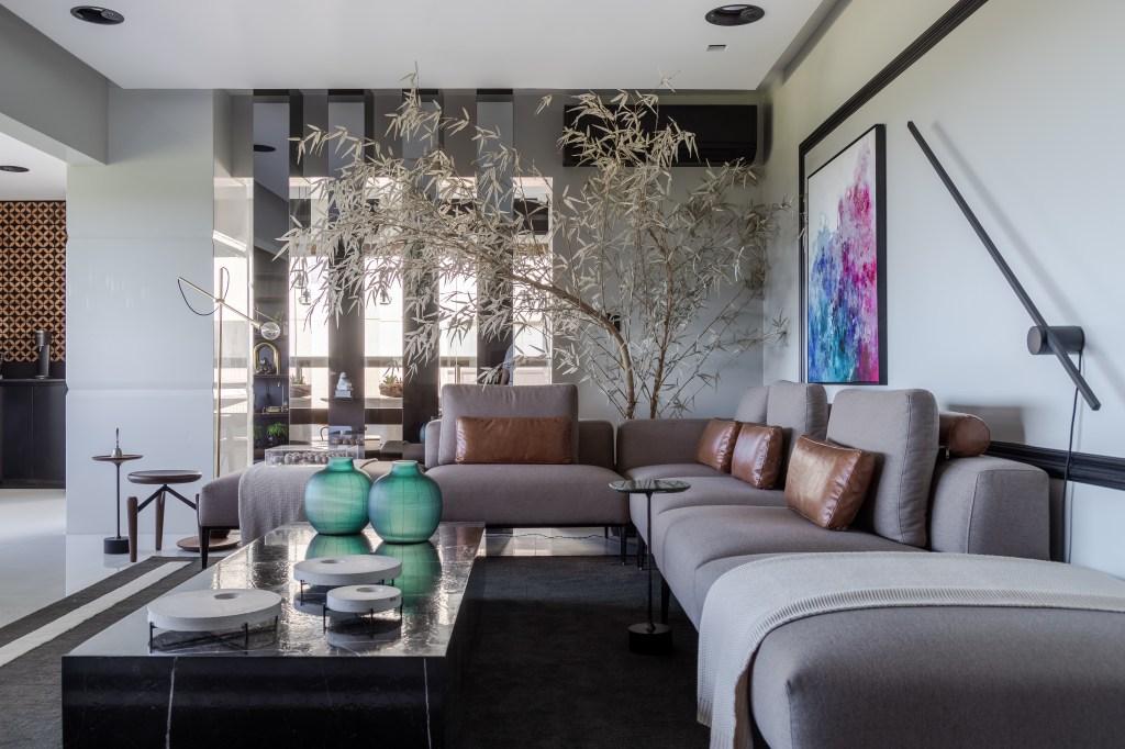 Living com sofá de canto de cor clara e almofadas em couro. Mesa de centro preta com vasos verdes circulares. Árvore decorativa com folhas brancas no canto direito