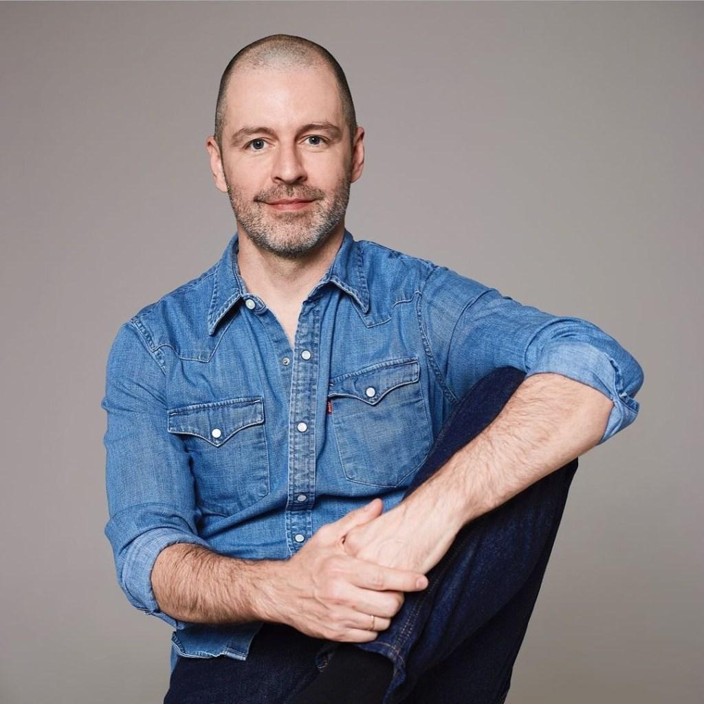 Homem branco, com a raspada e braba por fazer sentado, com um joelho sobre o banco com o braço esquerdo sobre ele.