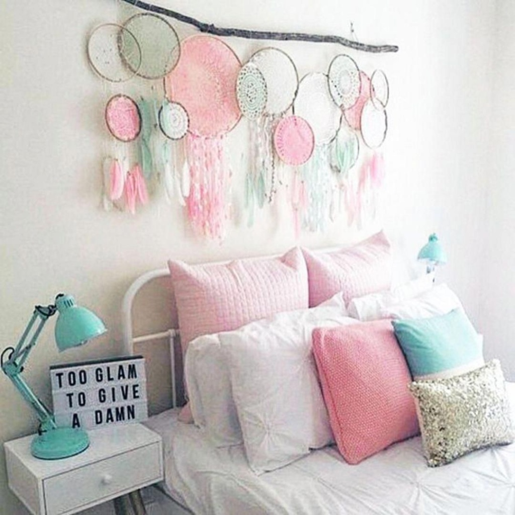 Quarto com cama branca um galho com vários aparadores de sonhos penduradose travesseiros rosas e azuis. Na parede branca