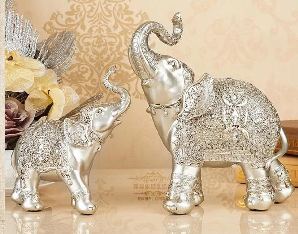 Dois elefantes prateados pequenos com as trombas levantadas, um de frente para o outro