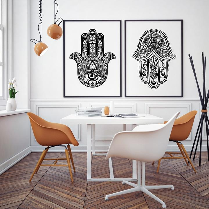 Sala de jantar com piso em madeira e parede branca. Mesa com quatro cadeiras, duas laranjas e duas brancas. Ao fundo, dois quadros com mãos hamsa em preto e branco