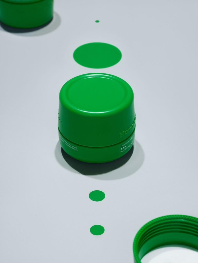 Produto de cuidado facial, com embalagem verde, cilíndrica em fundo branco azulado
