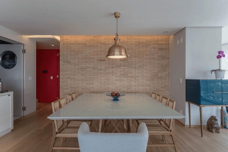 Sala de jantar, com parede de tijolos. À esquerda, porta colorida vermelha
