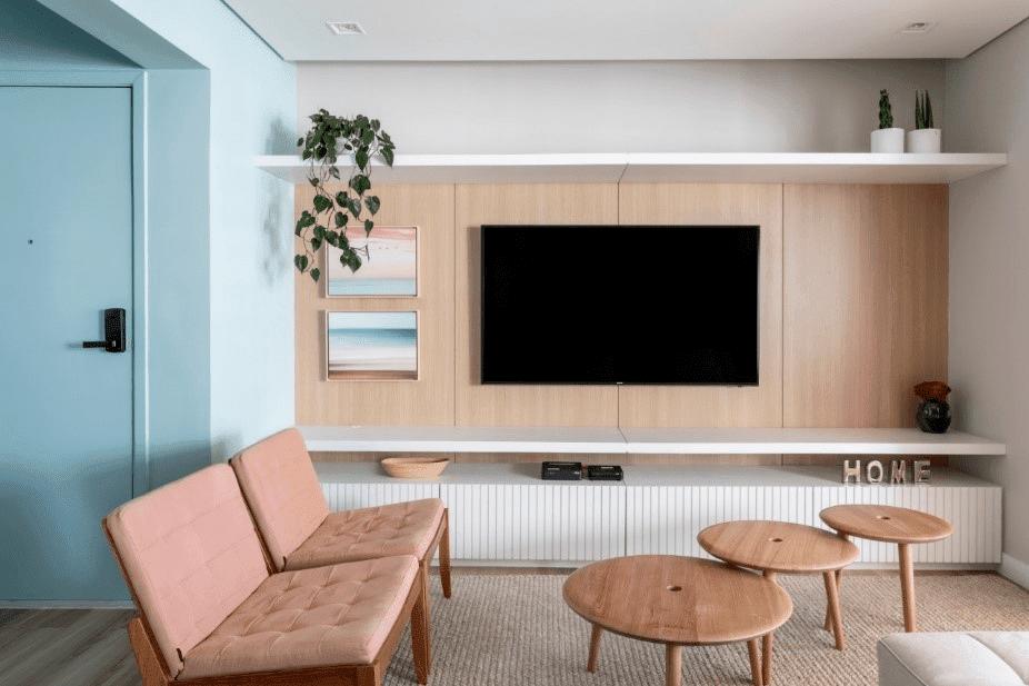 Sala de estar com Tv no painel de madeira clara, à esquerda a porta colorida turquesa