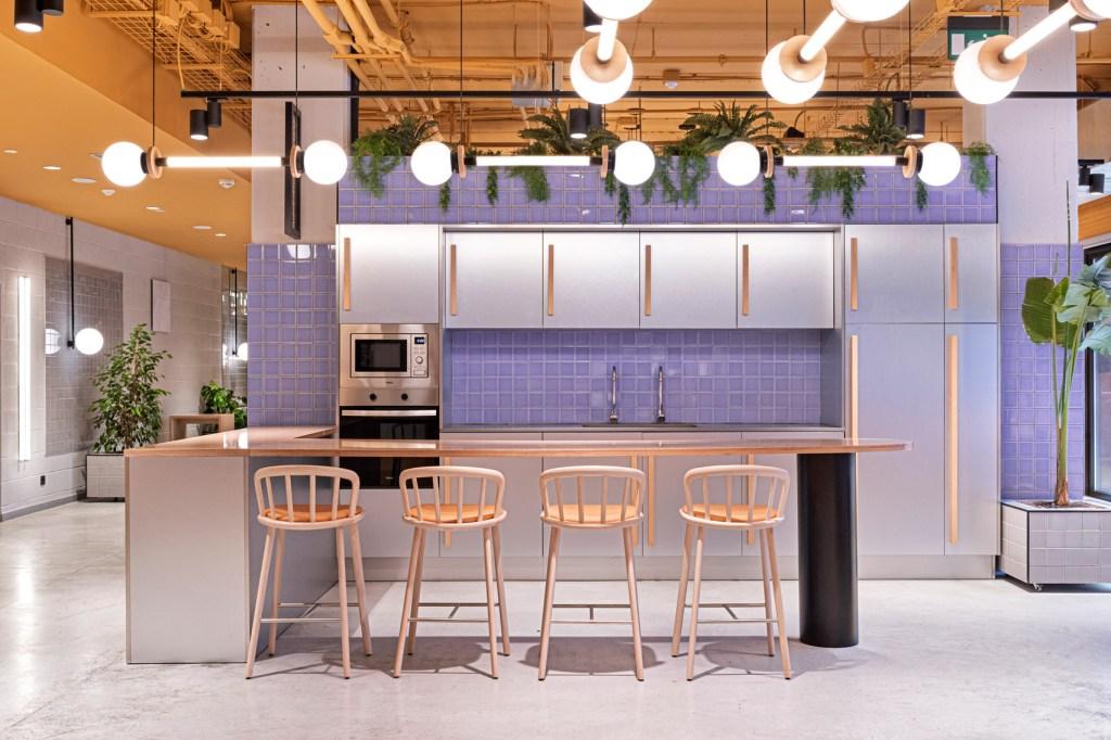 Cozinha roxa com móveis em prata e madeira, com bancada de madeira e acentos amarelo, no mesmo tom que o teto