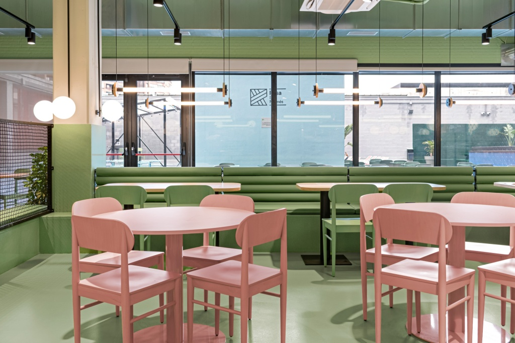 Sala com mesas e paredes verdes, com os acentos da parede da mesma cor, e mesas e cadeiras rosas