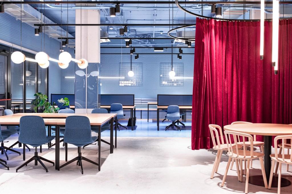 Sala de estudo com paredes azuis e matde do piso na mesma cor, com mesas de madeira e cadeiras azuis