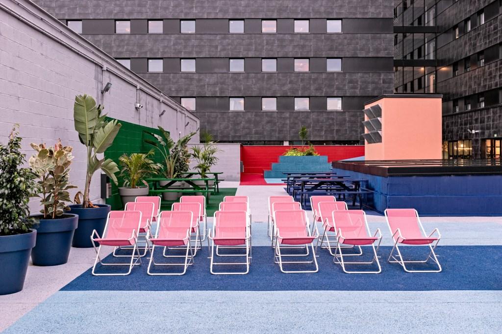 Terraço aberto com chão em tons de azul, com cadeiras de praia rosa, paredes cinzas, com parte pintada de ver, com mesas da mesma cor