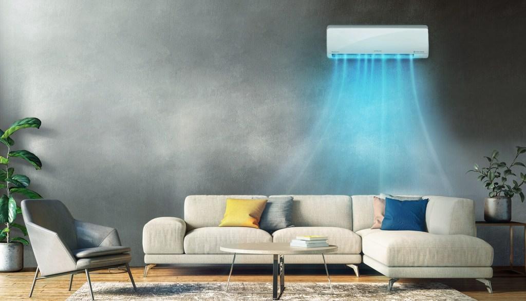 Sala com parede de cimento queimado e sofá claro. Ar condicionado ligado acima com raios azuis representando o ar frio