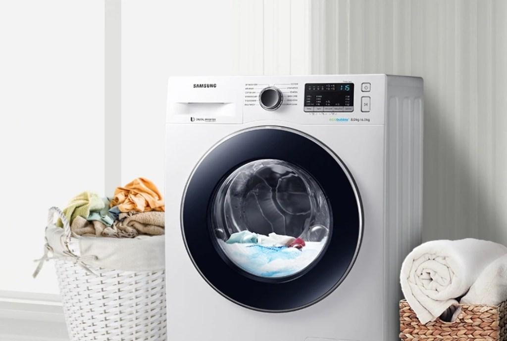 Máquina de lavar branca com cesto de roupas branco ao lado