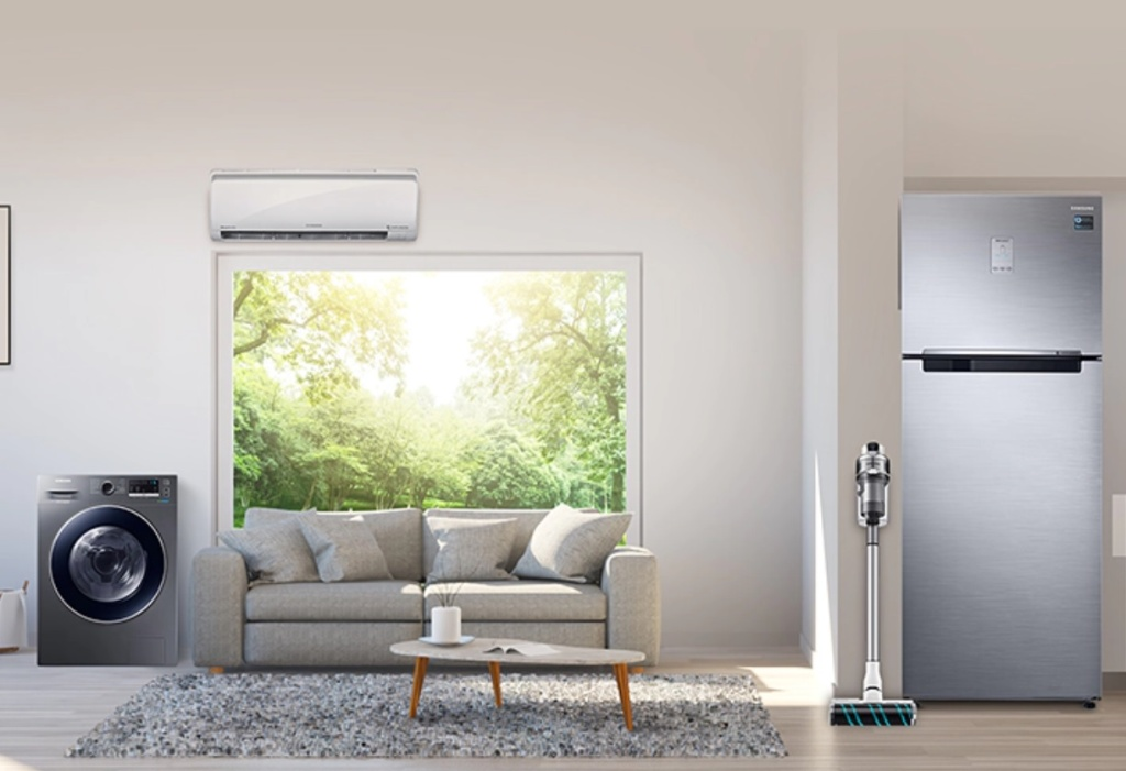 Living com sofá claro, piso em madeira e tapete cinza. Máquina de lavar à esquerda, ar condicionado acima da janela. Geladeira e aspirador de pó à direita