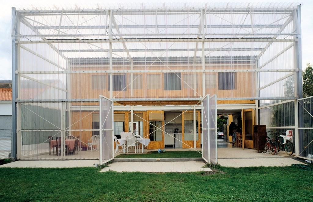 Casa amarela com estrutura tipo estufa na frente, criando área de lazer coberta