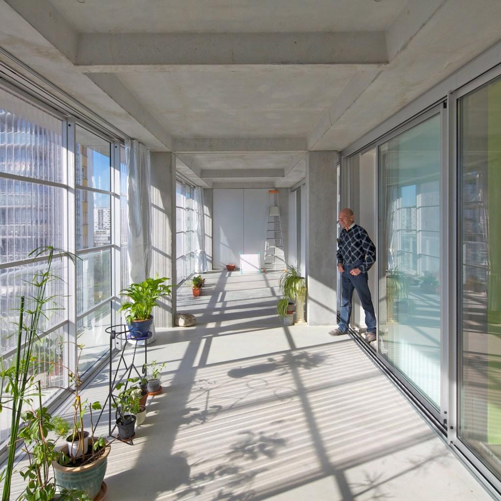 Grande varanda em concreto com portas de vidro de deslizar de um lado e janelas de vidro do outro. Homem parado na porta. Plantas perto da janela