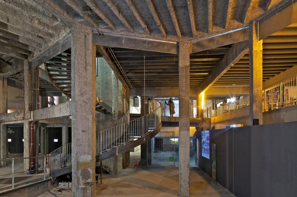 Construção em concreto com teto com textura. Escada curva também em concreto liga primeiro e segundo andar