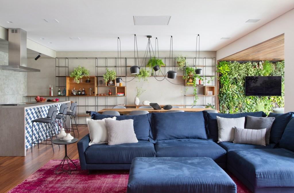 Living integrado com cozinha. Piso em madeira e paredes em cimento queimado. Sofá azul marinho modular com almofadas cinzas