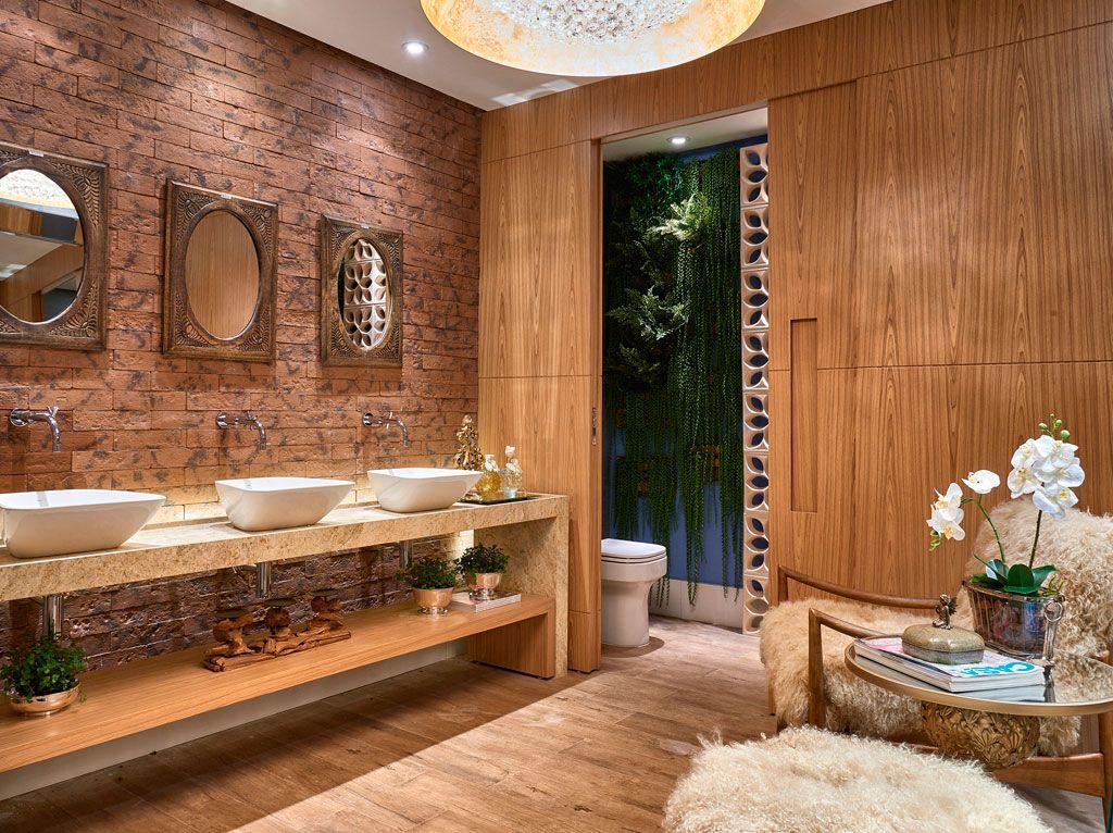Banheiro em madeira com parede em tijolos. Três espelhos redondos acima de três cubas.