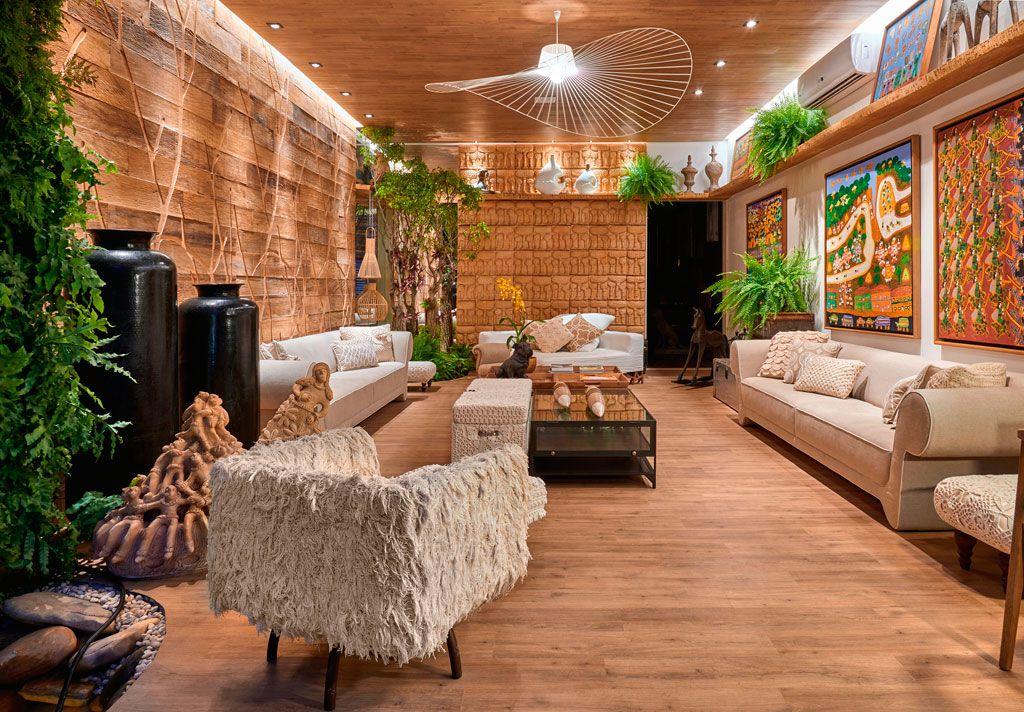 Living em madeira com paredes de tijolos e piso em madeira. Sofás e poltronas brancas. Quadros nas paredes