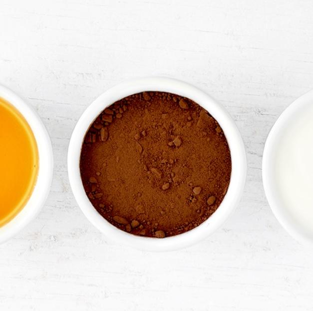 Tigela com cacau em pó. Tigela com mel. Tigela com creme branco.