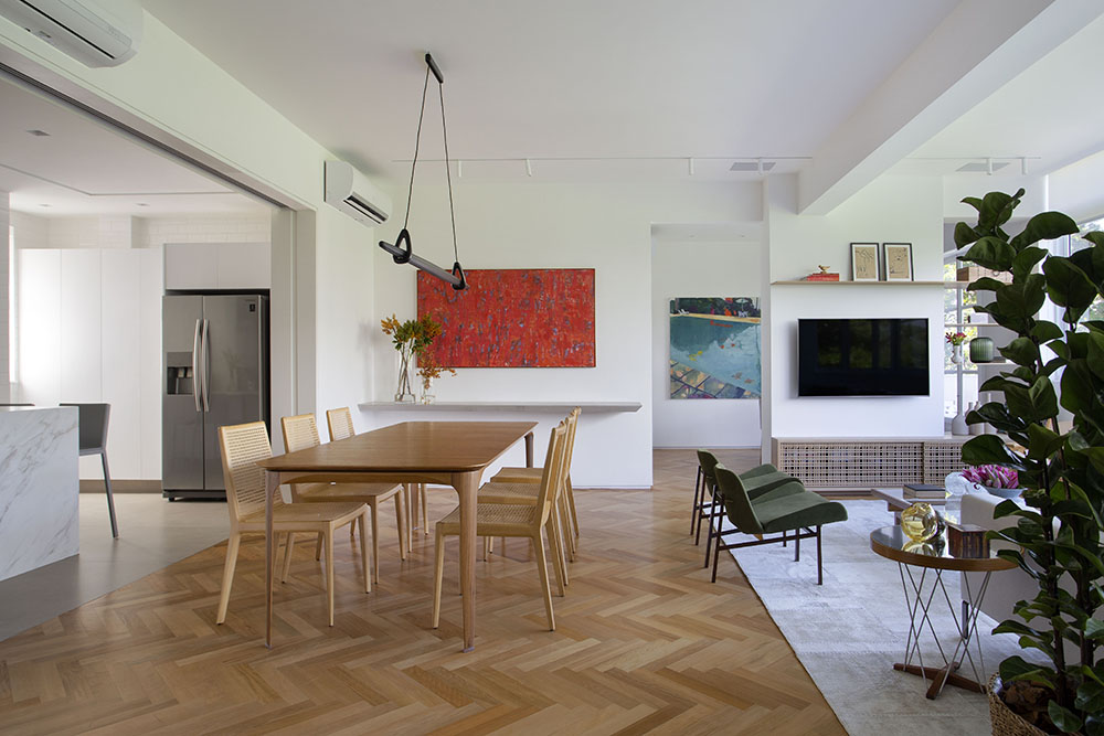Living com sala de jantar, estar e cozinhas integrados. Mesa de madeira e cadeiras de madeira no centro. Piso de taco.