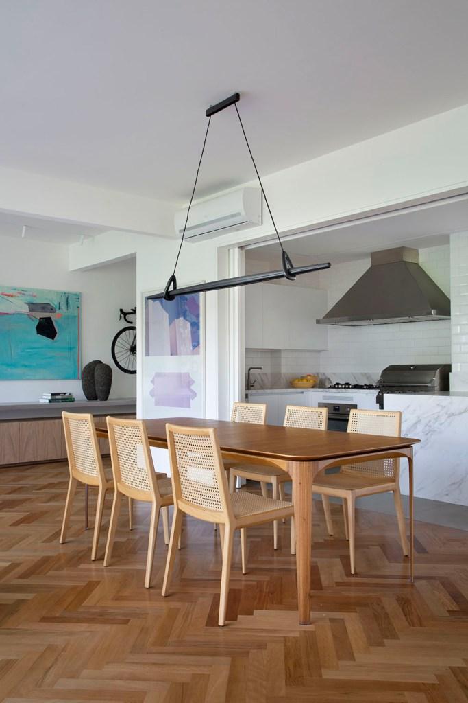Estar com cozinha integrada. Mesa em madeira com cadeiras de madeira. Churrasqueira na cozinha.