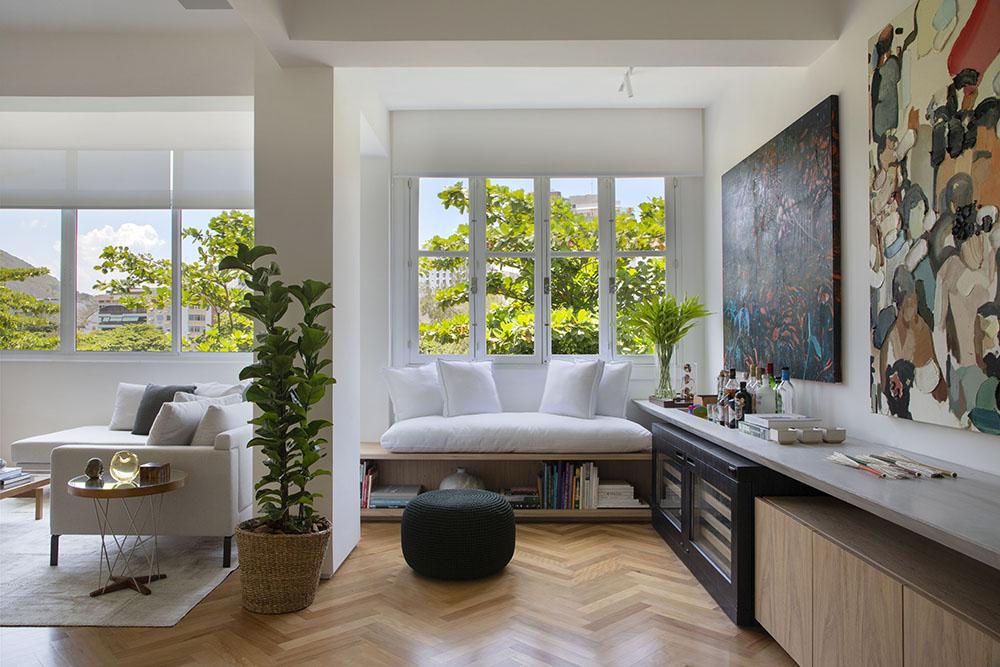 Estar com quadros na parede. Sofá branco embaixo da janela. Vaso de planta à esquerda