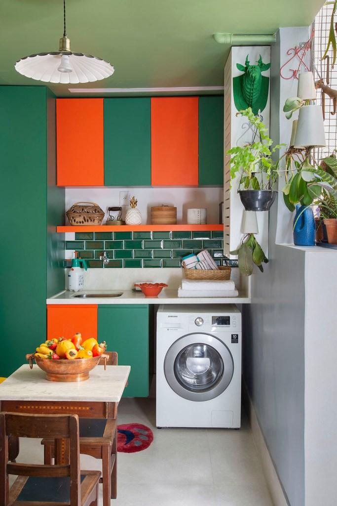 Lavanderia com armários verdes e laranjas. Máquina de lavar encaixada. Plantas penduradas