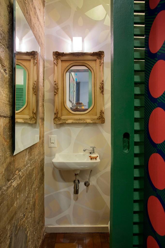Lavado com espelho com moldura neoclássica. Papel de parede geométrico