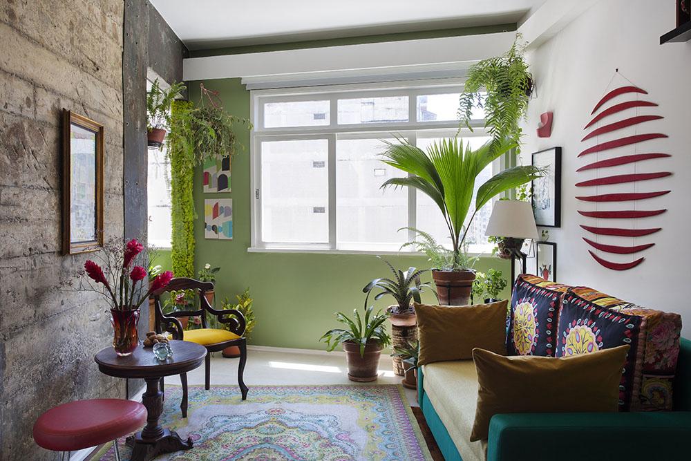 Living com sofá verde. Parede de concreto aparente. Plantas em vasos ao fundo.
