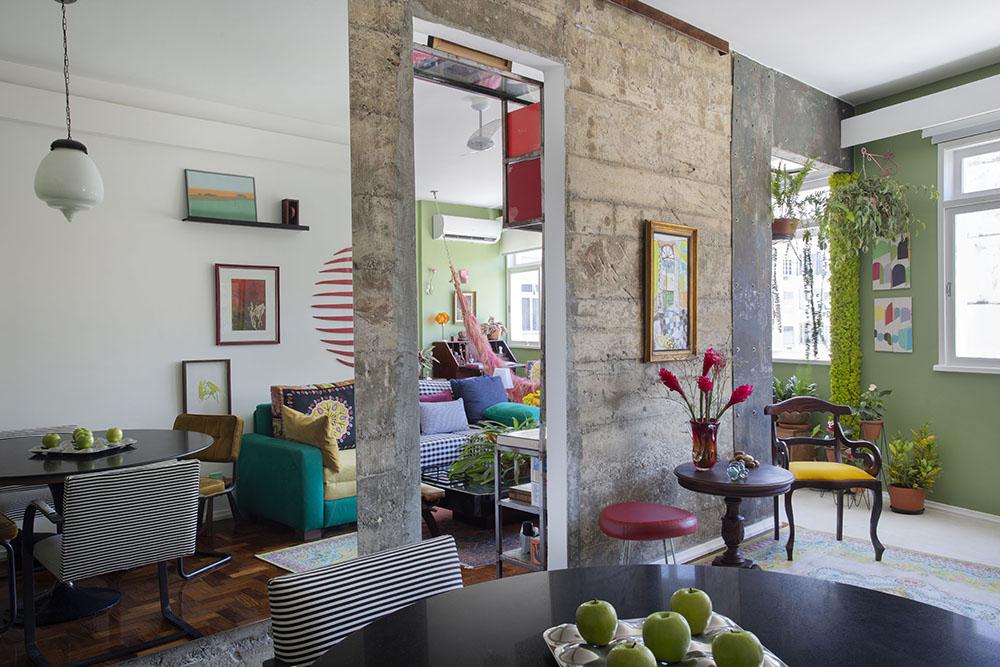 Living com parede de concreto aparente. Mesa circular preta. Parede verde. Pela porta da parede de concreto, sofá azul e branco de listrinhas.