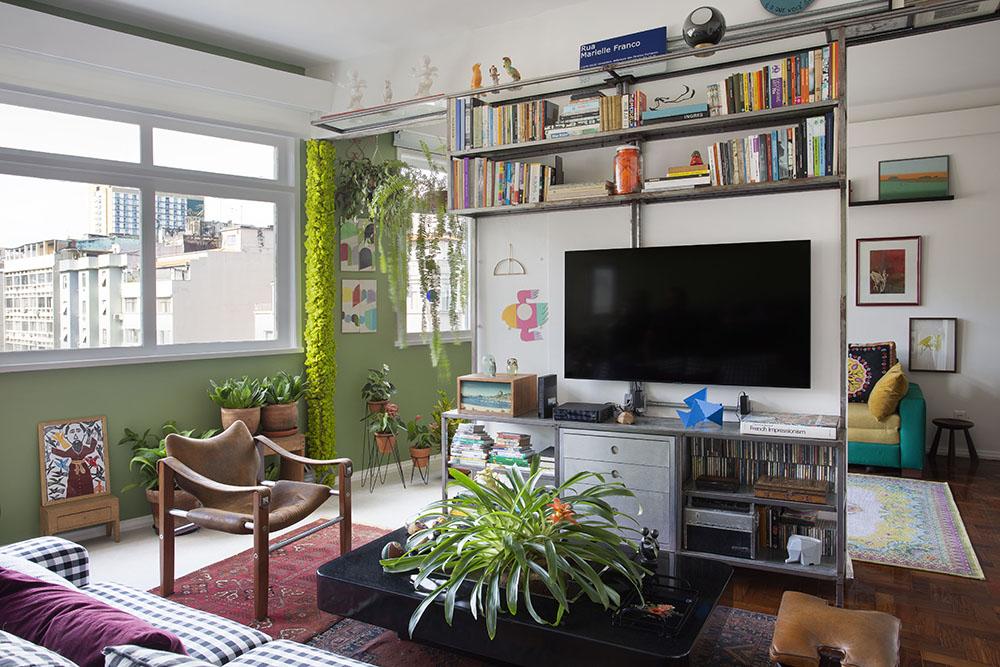 Sala de tv com sofá listrado, móvel cinza com livros e tv. Tapete vermelho. Cadeira de madeira. Plantas ao fundo