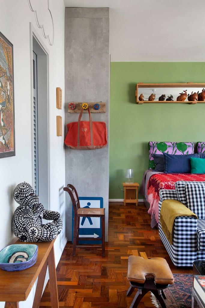 Cama de casal com travesseiros estampados. Piso de taco. Objetos decorativos em madeira. Aparador com enfeites.