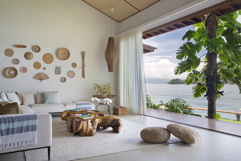 Estar com piso de porcelanato e acessórios de palha nas paredes. Sofá claro e mesa de centro rústica em formato de tronco