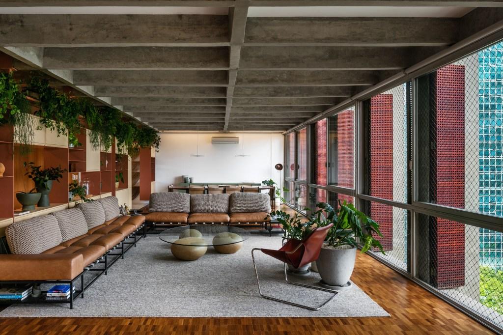 Living com piso em madeira e tapete cinza. Dois sofás em couro amarelo com almofadas claras. Estante multifuncional à esquerda. Plantas no andar de cima. Grandes janelas de vidro