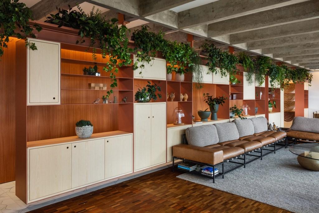 Móvel multifuncional com armários e nichos. Plantas no andar de cima. Sofá em couro amarelado