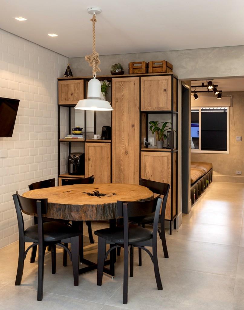 Sala de estar com mesa em madeira e cadeiras pretas. Estante vazada em madeira e metal. Parede revestida de tijolinhos brancos. Piso cinza