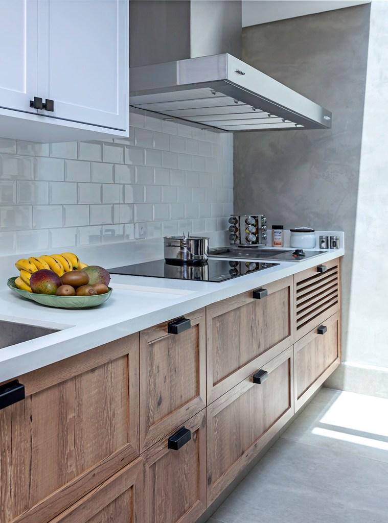 Bancada branca com armários em madeira. Cooktop preto e cooktop prata