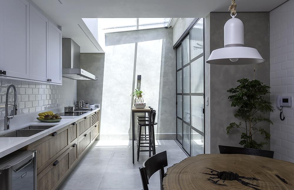 Cozinha com varanda coberta e integrada. Balcão e armários brancos à esquerda, mesa de madeira à direita, mesa alta com bancos no centro. Revestimento em cimento