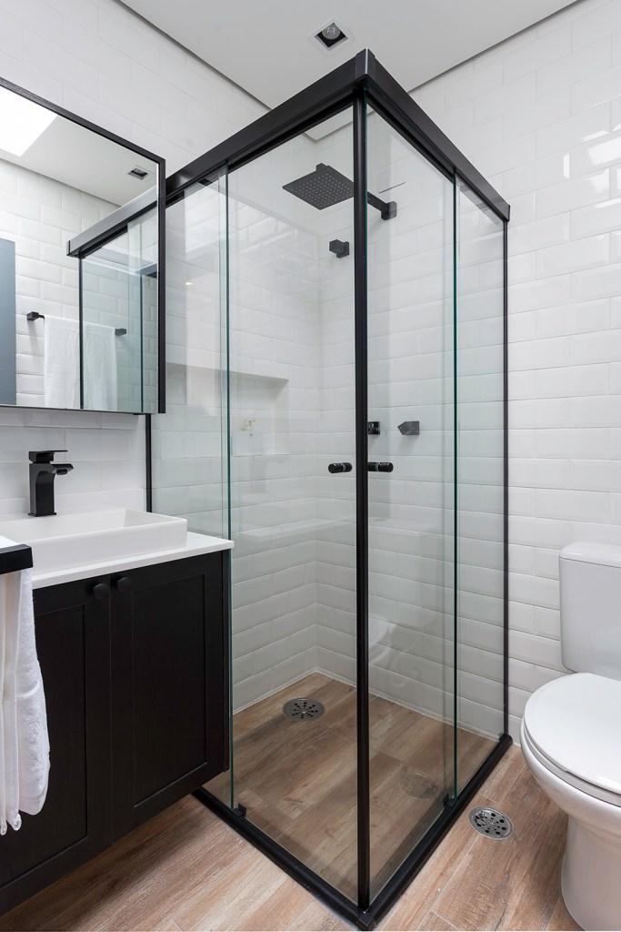 Banheiro revestido de tijolinhos brancos. Box em vidro com detalhes pretos