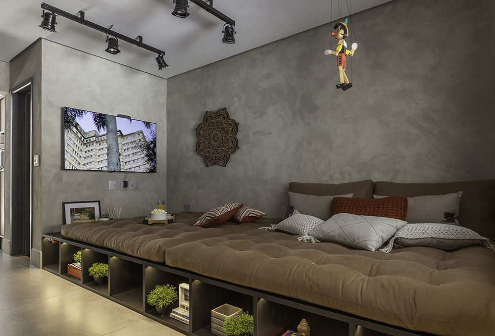 Estar com móvel em madeira com nichos e almofadas em cima para sofá. Marionete de pinóquio suspensa do teto.