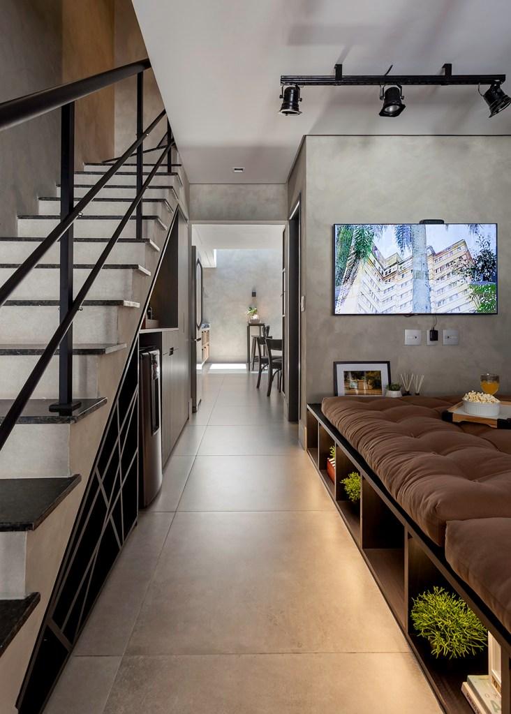 Móvel em madeira com almofadas à direita. Escada com nichos à direita.