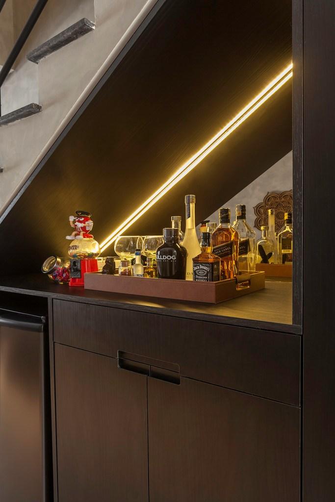 Espaço embaixo da escada utilizado como bar. Nicho triangular com espelho ao fundo e led. Bandeja com bebidas e copos.