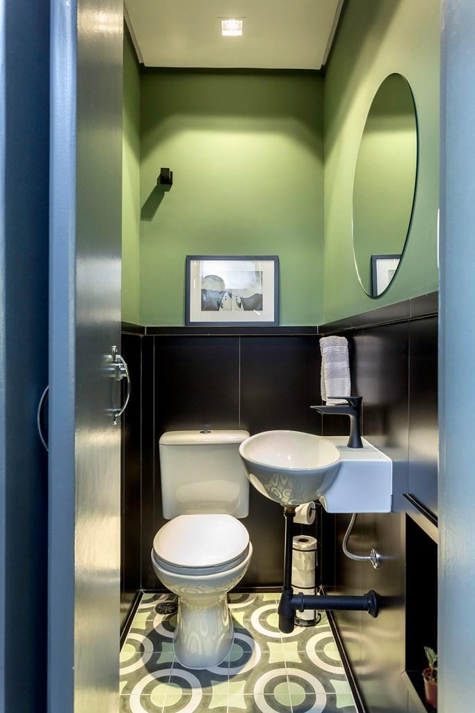 Lavabo verde com meia parede revestida em preto. Espelho circular à direita