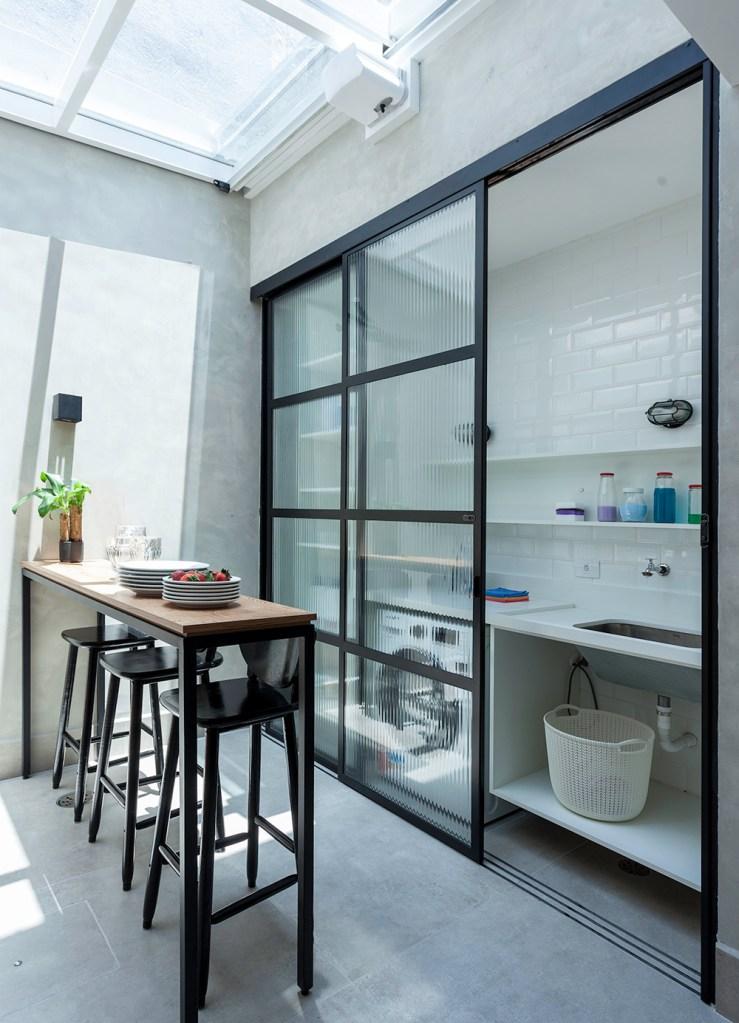 Varanda coberta com cobertura de vidro. Mesa em madeira alta com bancos pretos. Lavanderia atrás de porta de vidro.
