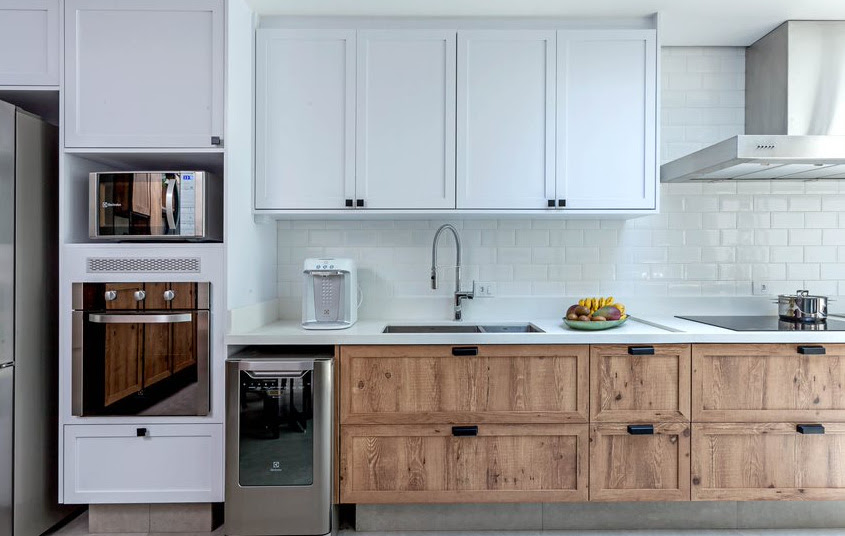 Cozinha com armários brancos. Armários de baixo em madeira.