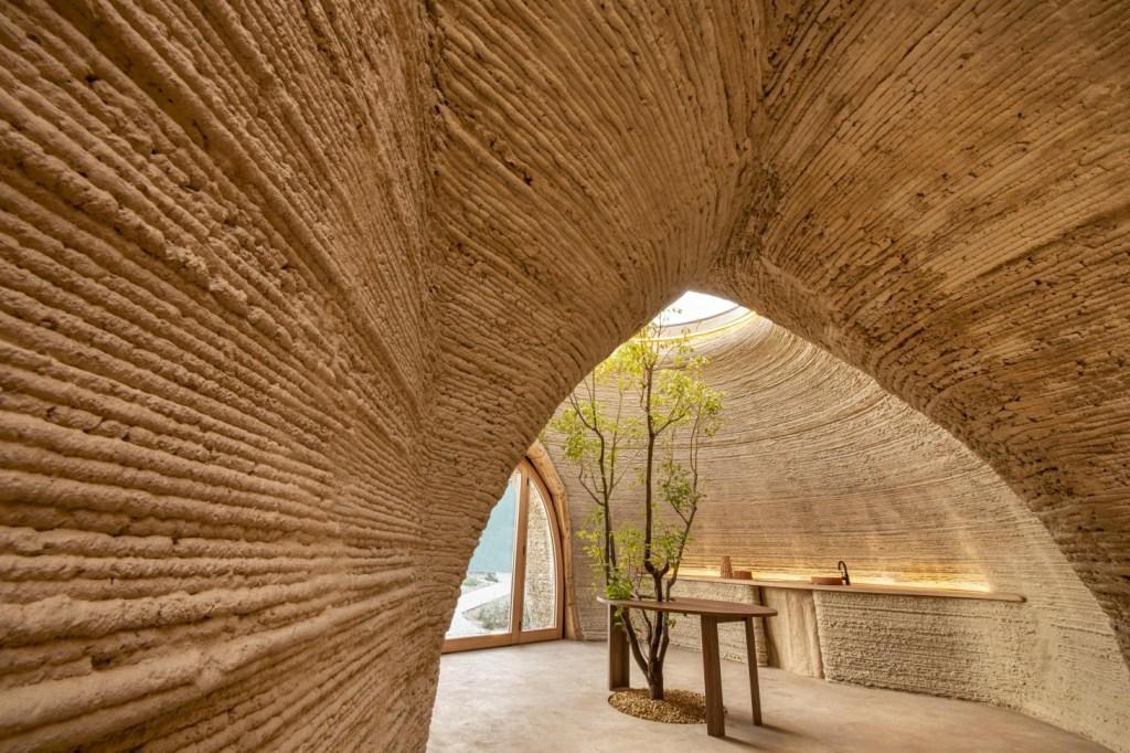 Interior do habitat. Corredor com paredes com sulcos finos levando ao espaço central, com mesa e cadeira. A mesa envolve uma árvore