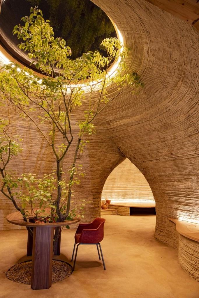 Interior do habitat. Árvore no centro envolta por mesa e cadeira vermelha.