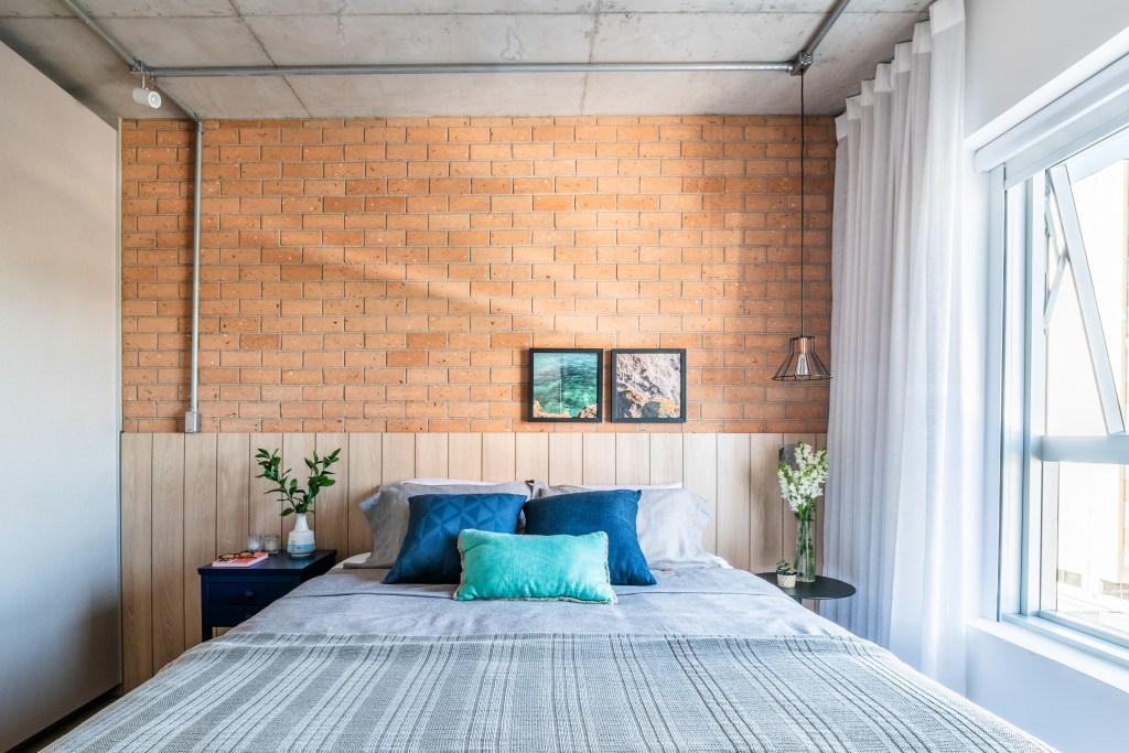 Quarto de casal estilo industrial, com cabeceira de ripas de madeira, com meia parede de tijolinhos laranja.