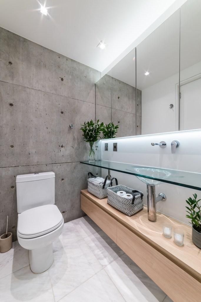 Banheiro estilo industrial, com parede em cimento queimado, e bancada da pia de vidro, com móvel de madeira clara abaixo